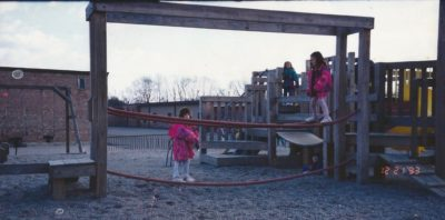 A very young Jessica walks across a tightrope at a playground.